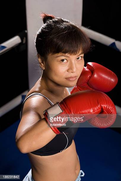 Young woman practicing boxing in a boxing ring