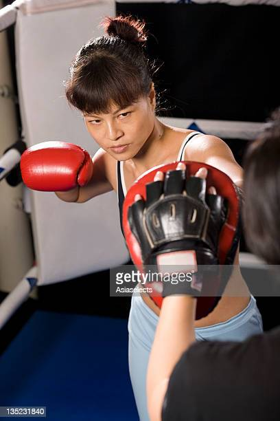 Young woman practicing boxing with her instructor