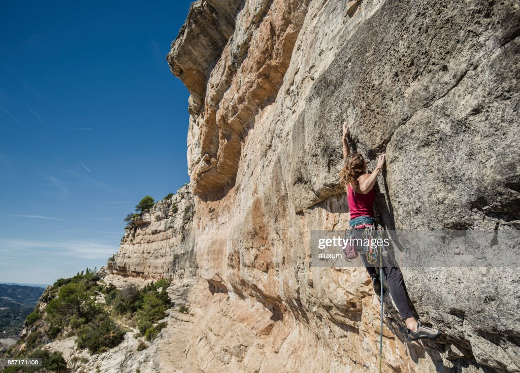 Young woman practicing rock climbing : Stock Photo