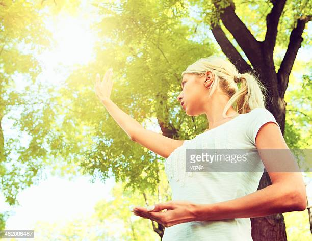 Young Woman Practicing Tai Chi Outdoors.