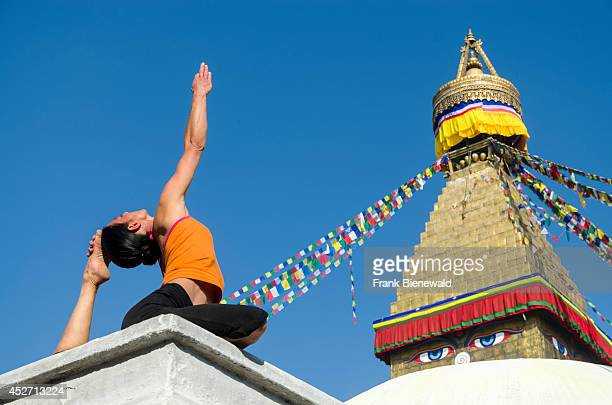 Young woman practicing yoga at Boudnath Stupa showing the pose kapotasana dove pose / pigeon pose Boudnath with its huge Stupa is the center for...