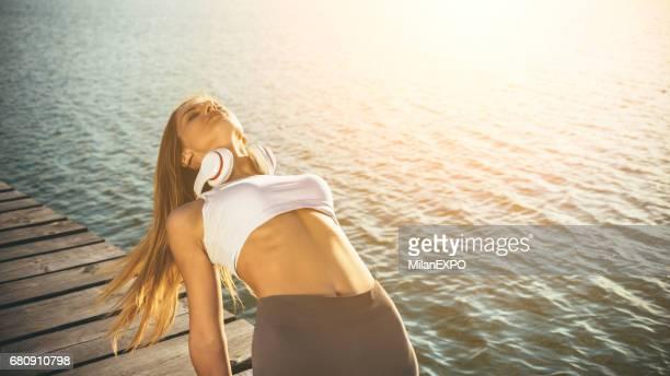 Junge Frau praktizieren Yoga am See