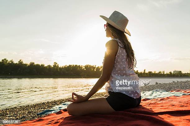 Young woman practicing yoga at the riverside at sunset