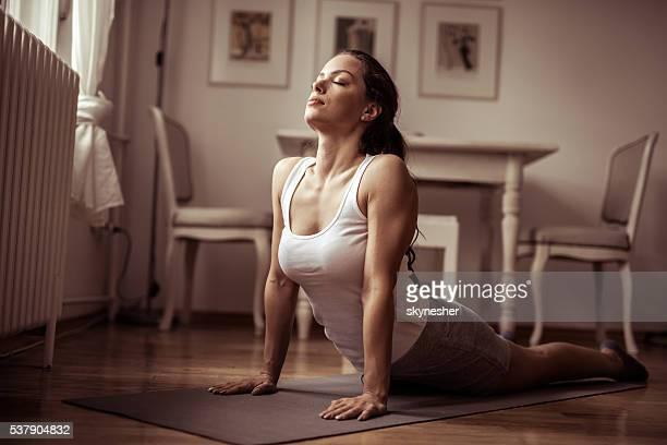Junge Frau üben yoga-Kobra-position in ganz wie zu Hause fühlen.