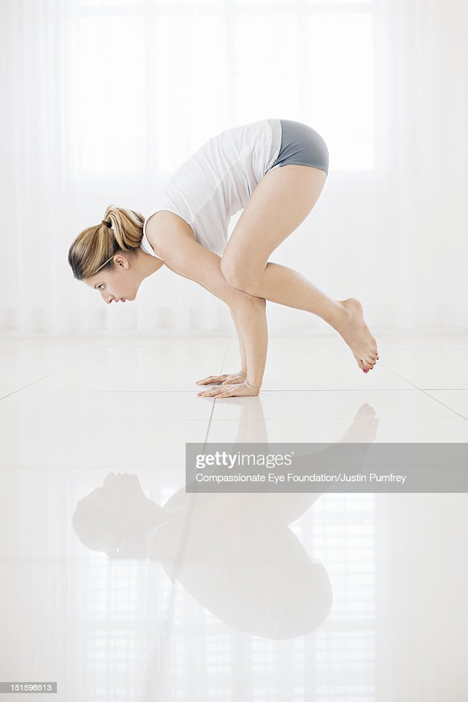 Young woman practicing yoga in living room : Stock Photo