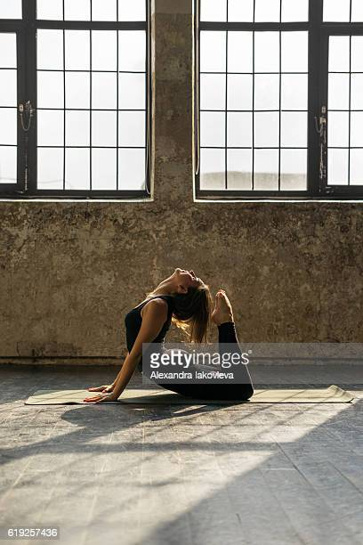 Young woman practicing yoga in urban loft: Cobra Pose (Bhujangasana)