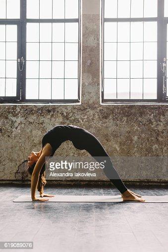 Young woman practicing yoga in urban loft: Upward Bow Pose