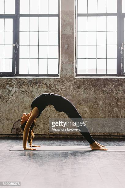 Young woman practicing yoga in urban loft: Upward Bow Pose