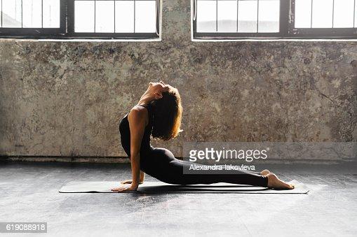 Young woman practicing yoga in urban loft: Upward Facing Dog