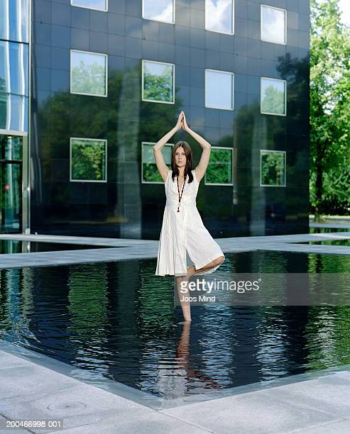 Young woman practicing yoga in water feature outside office building