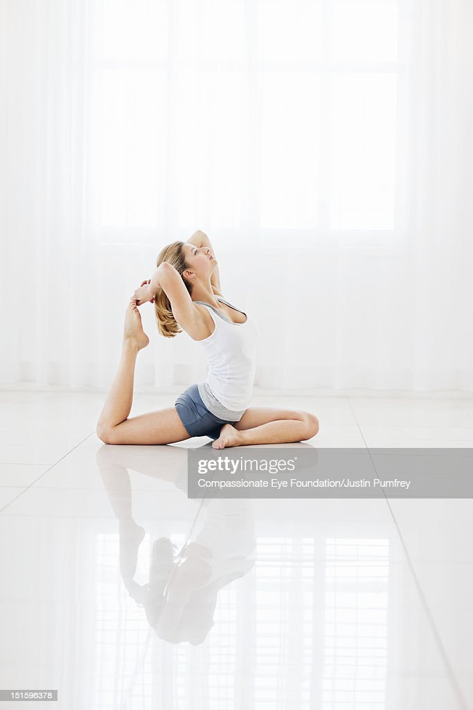 Young woman practicing yoga indoors : Stock Photo