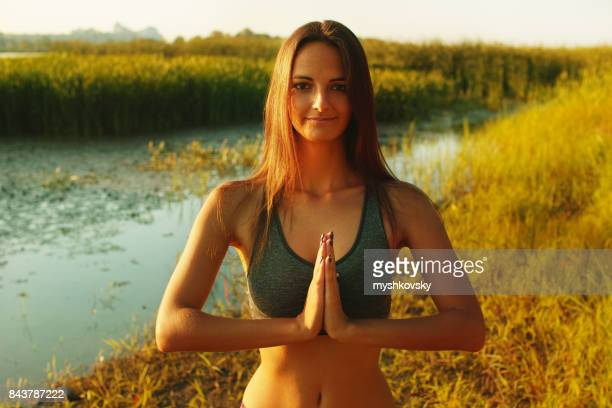 Young woman practicing yoga near a lake