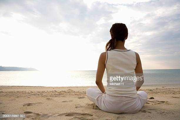 Young woman practicing yoga on beach, rear view