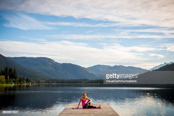 Jeune femme de pratiquer l'yoga sur le quai au bord du lac.