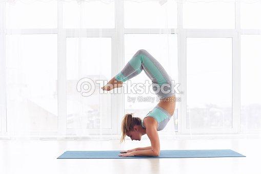 e2ba0f9253c32 Young woman practicing yoga, standing in Vrischikasana Scorpion pose at the  yoga studio