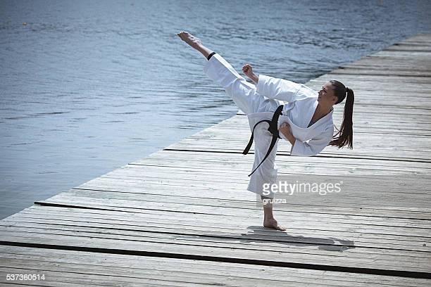 Junge Frau Übungen Karate im Freien