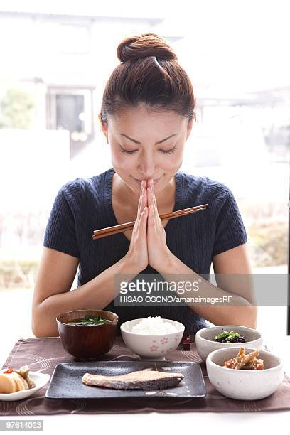 Young Woman Praying for Breakfast, Holding Chopsticks