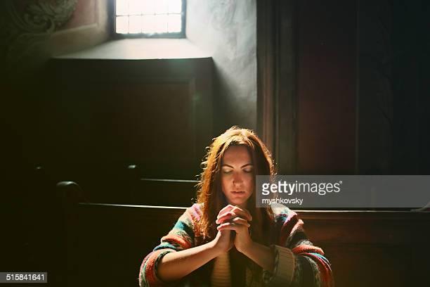 Jovem mulher rezar na Igreja