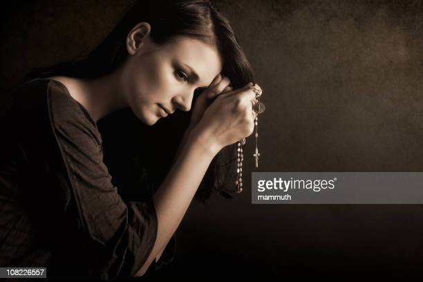 Young woman praying with rosary