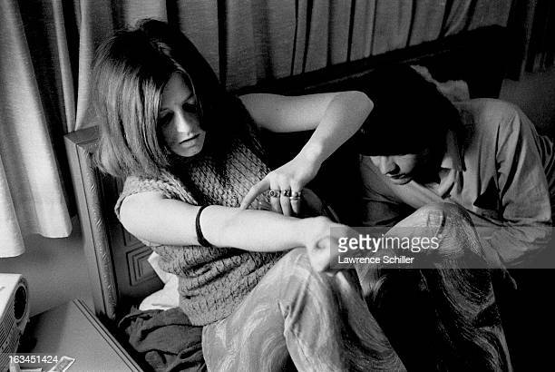 A young woman prepares to inject LSD using a syringe Los Angeles California 1966
