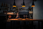 Food and wine on the bar counter at the stylish apartments. Young woman preparing dinner in the modern home kitchen in the evening. Romantic blonde on the background. Painted heart on the wall