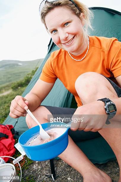 Young woman preparing food at camping