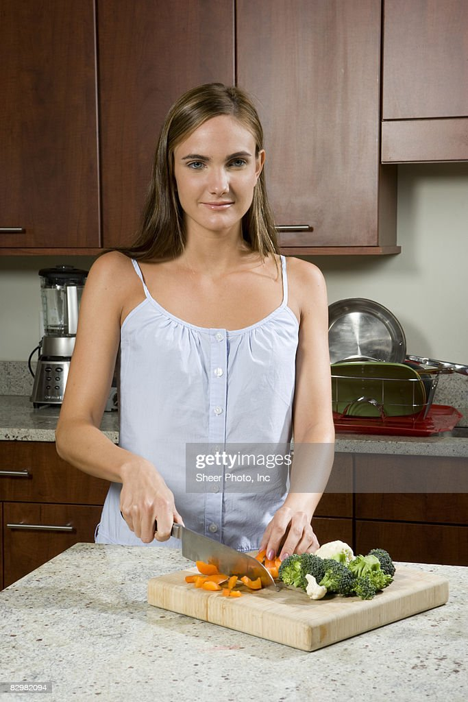 Young woman preparing food in kitchen : Stock Photo