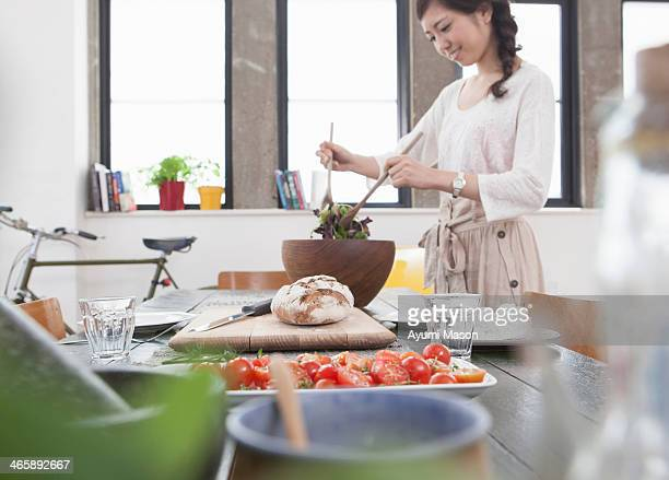 Young woman preparing meal at table