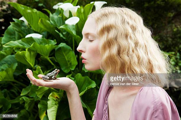 Young woman preparing to kiss frog.