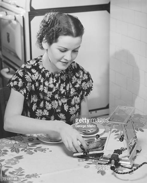 Young woman preparing toasts at kitchen table (B&W),