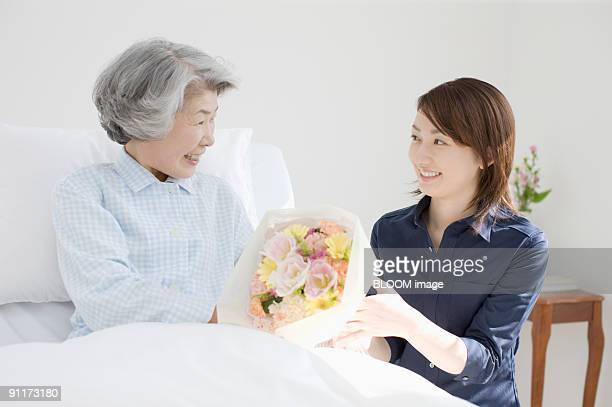 Young woman presenting bunch of flowers to senior woman in bed