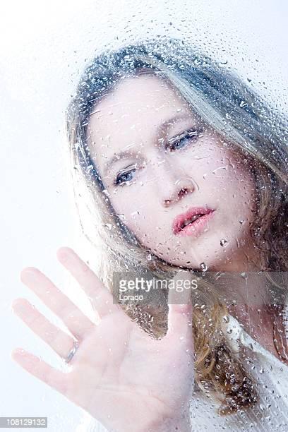 Giovane donna stiratura mano contro finestra di cabina doccia