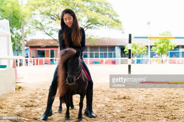 Young woman pretending to ride a pony