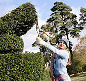 Young woman pruning hedge with shears, smiling