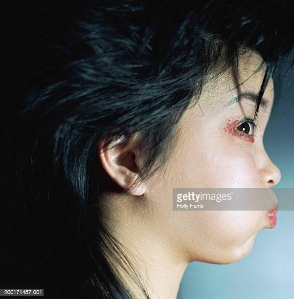 Young woman puffing cheeks out, profile