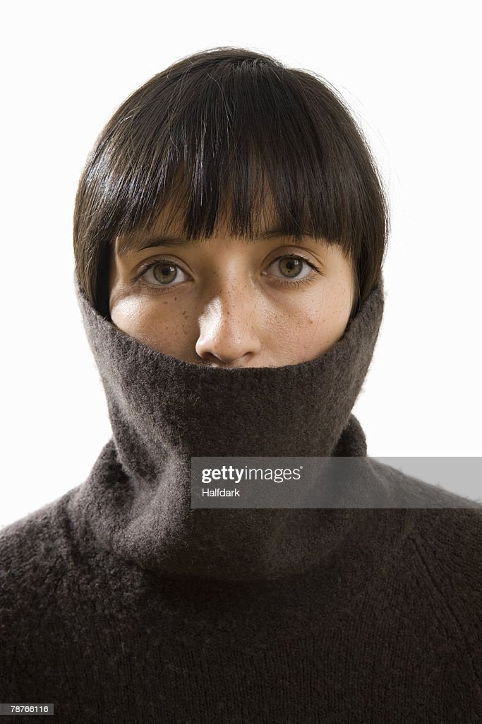 A young woman pulling a turtleneck over her head