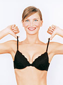 Young woman pulling bra straps, smiling, portrait