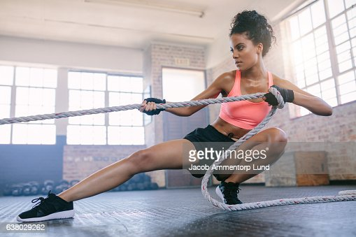 Young woman pulling rope at gym. : Stock-Foto