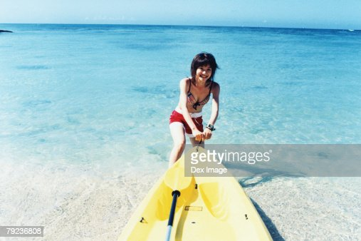 Young woman pulling sea kayak into water : Stock Photo
