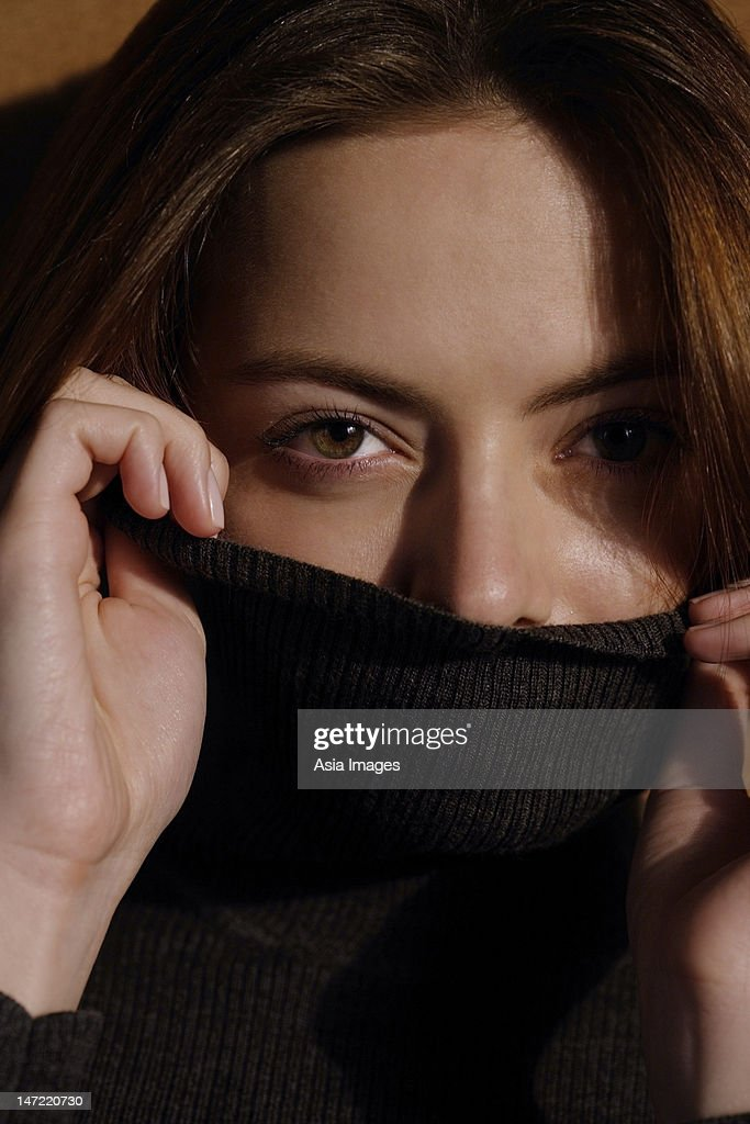 Young woman pulling turtleneck over face
