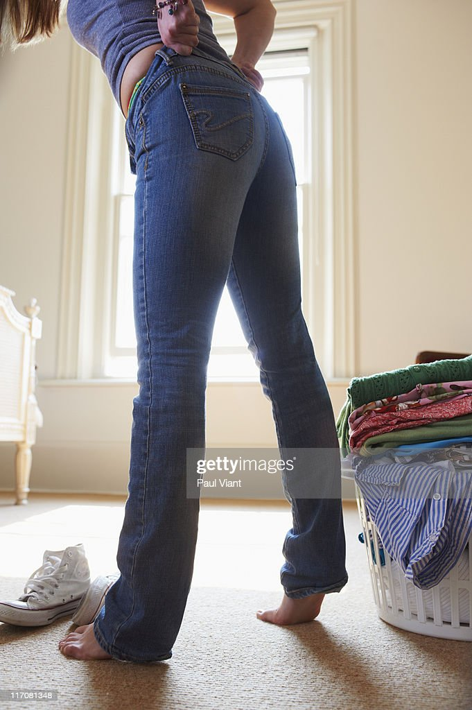 young woman pulling up tight jeans : Stock Photo