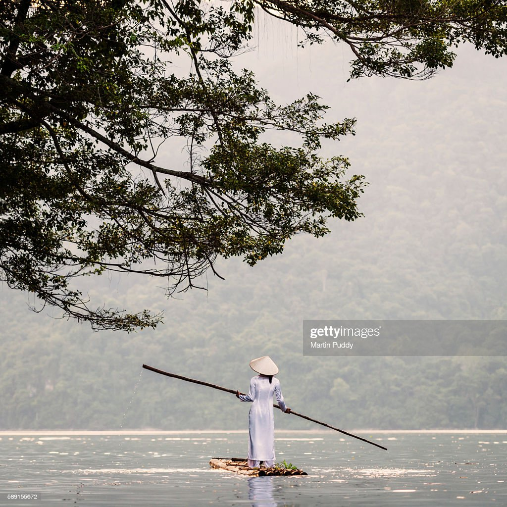 young woman punting bamboo raft across lake