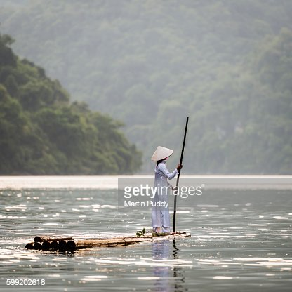 young woman punting bamboo raft across lake