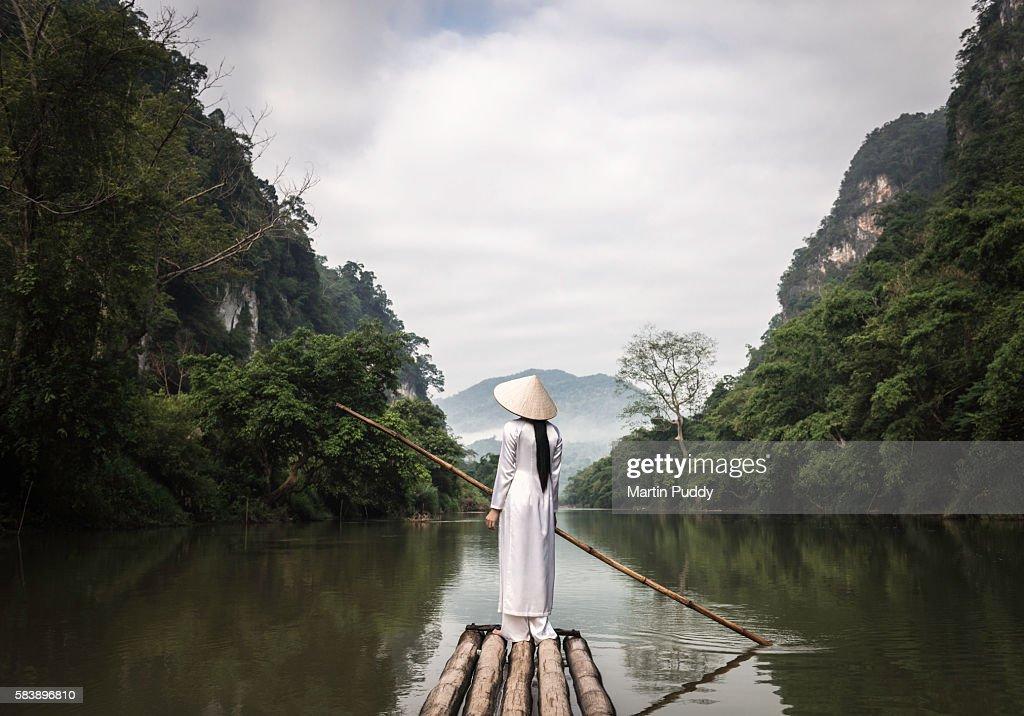 young woman punting bamboo raft along river