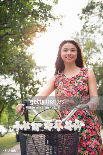 Young woman pushing a bike, smiling.. : Stock Photo