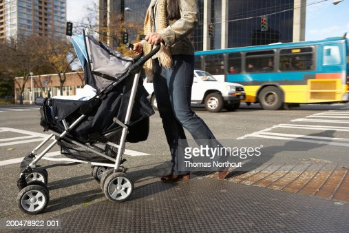 Young woman pushing baby stroller on urban sidewalk, low section : Stock Photo