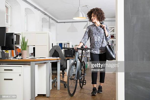 Young woman pushing bicycle in office