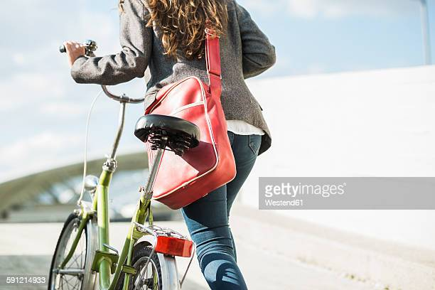 Young woman pushing bicycle