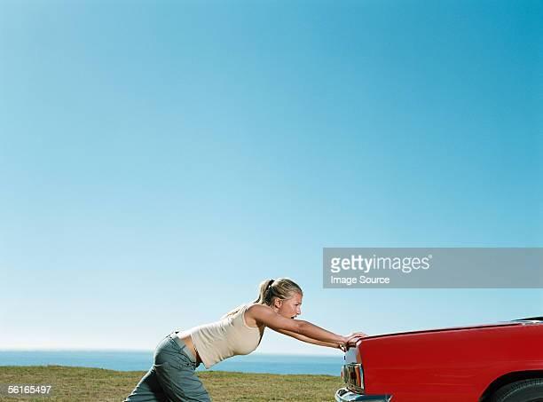 Jeune femme en poussant voiture