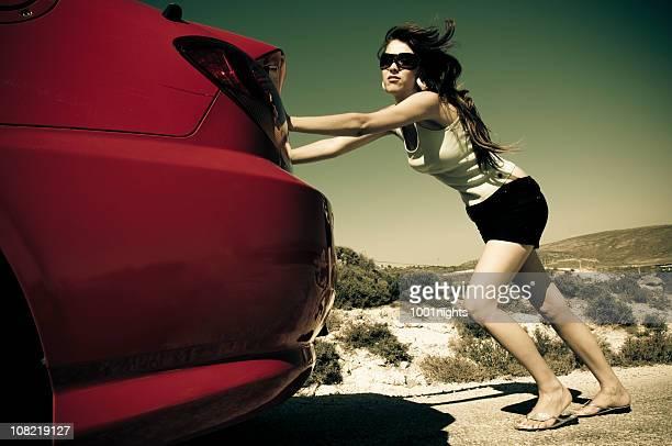 Jeune femme en poussant voiture rouge le long de la route dans le désert